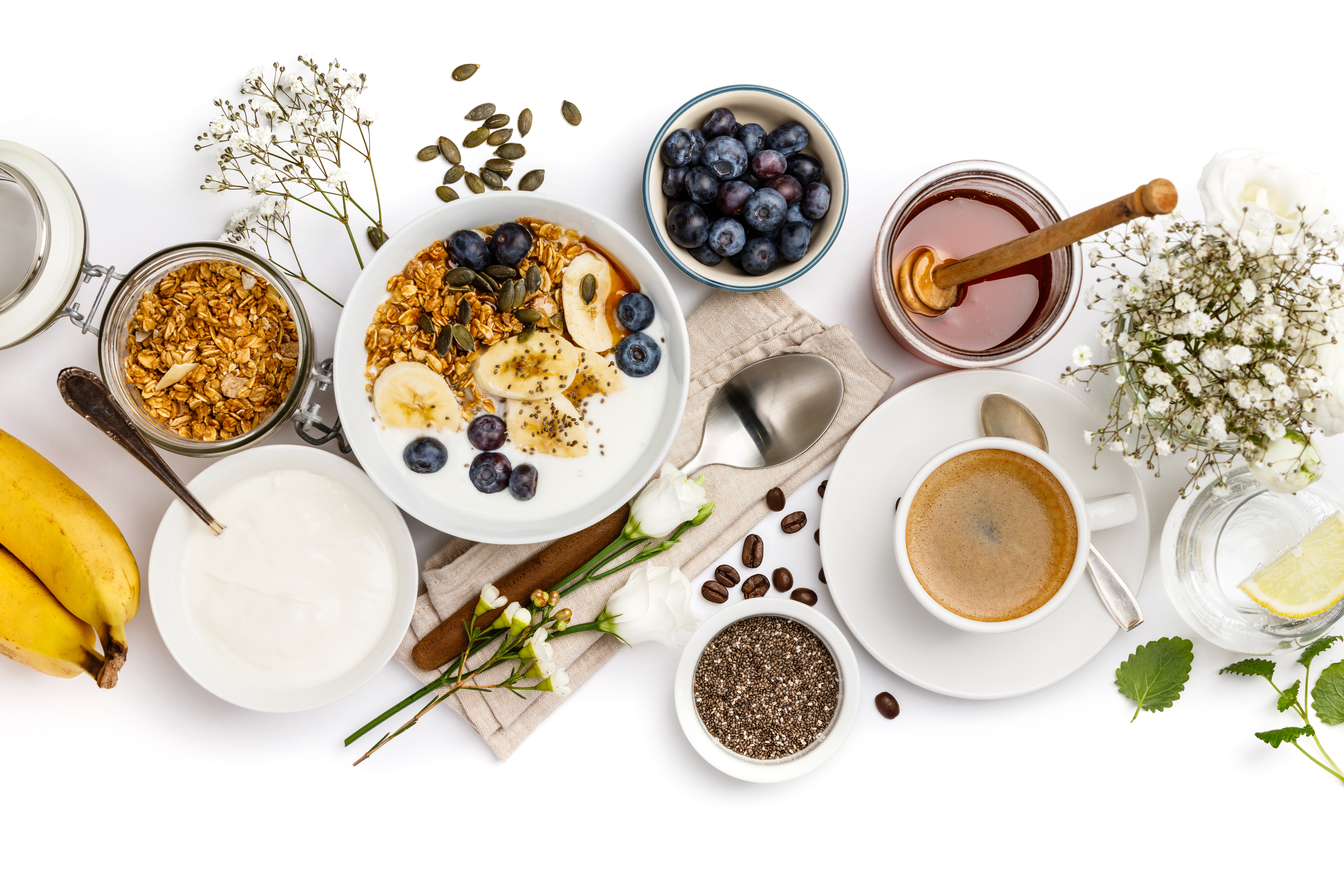 Healthy breakfast set. Oat granola with yogurt, honey, fresh bananas, blueberries, chia seeds in bowl  and cup of coffee on white background, top view